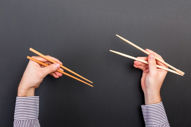 Creative image of wooden chopsticks in two male hands on black