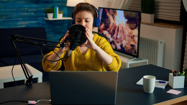 ビデオvlogを記録するソーシャルメディアでのライブ中に話す準備をしているヘッドフォンを持ったクリエイティブなインフルエンサー。スタジオからのオンエアオンライン制作インターネット放送ショーホストストリーミングポッドキャストコンテンツ
