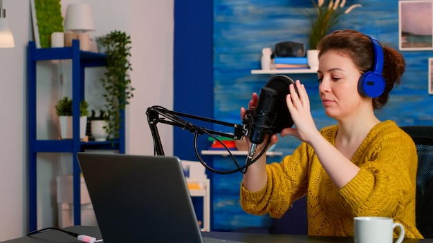 ソーシャルメディアの録画ビデオvlogでライブ中に話す準備ができているヘッドフォンを備えたクリエイティブなインフルエンサー