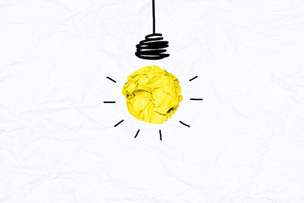 Creative iyellow crumpled paper light bulb on white recycle papaer background.