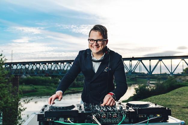 Creative joyful guy mixing track under the cloudy sky