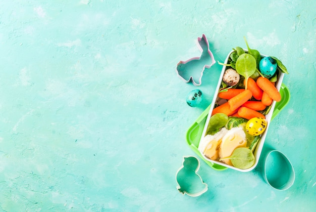 Creative kids breakfast lunch box for easter, sandwiches with cheese, fresh vegetables - cucumbers, carrots, spinach, colorful quail eggs. light blue table, copy space top view