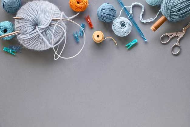 Creative knitting hobby wall in pastel colors on grey paper with copy-space