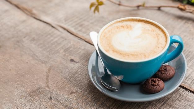 木製の机の上の2つの焼きクッキーと創造的なカフェラテアートコーヒーカップ Premium写真