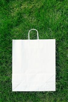 緑の芝生で作られたクリエイティブなレイアウト構成フレーム、ハンドル付きクラフト紙バッグ、フラットレイ、ロゴのコピースペース。