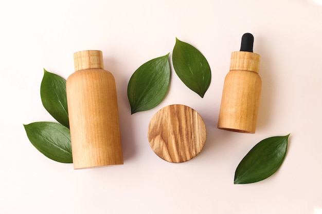 Creative layout from the wooden cosmetics containers with fresh green leafs around.pretty pastel colors,natural materials.organic concept.