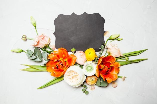 창의적인 레이아웃. 아름다운 꽃, 잎, 복사 공간이 있는 사진 한가운데의 문장 방패