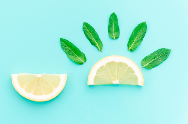 Creative layout of lemon pieces with mint leaves