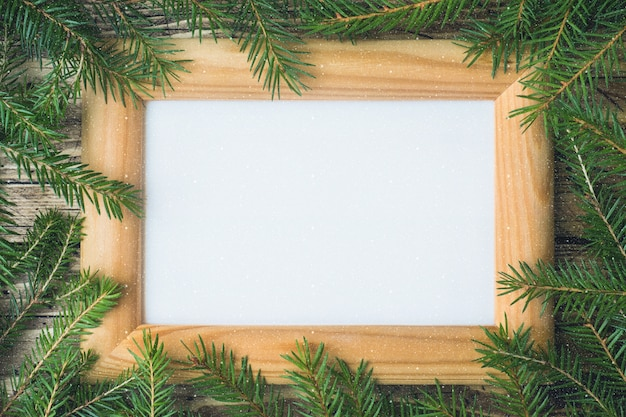 Creative layout made of christmas tree branches with paper card note.