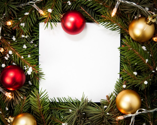 Creative layout  made of fir tree branches with white square shape paper and snowflakes christmas lights and baubles christmas and new years card concept flat lay top view