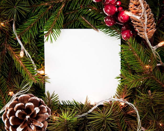 Creative layout  made of fir tree branches with white square shape paper and snowflakes christmas lights and pinecone christmas and new years card concept flat lay top view