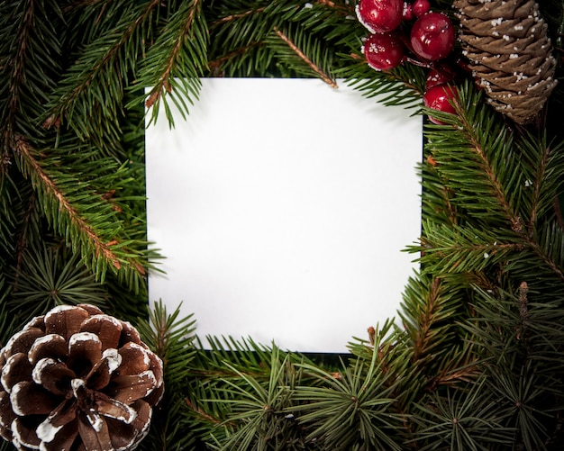 Creative layout  made of fir tree branches with white square shape paper and snowflakes and pinecone christmas and new years card concept flat lay top view