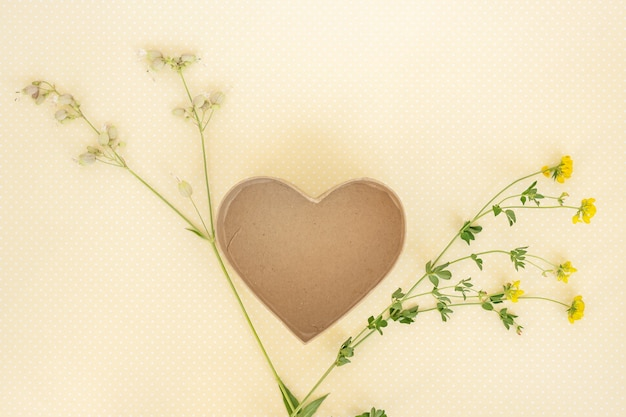 Creative layout made of flowers and leaves with heart box template. flat lay.