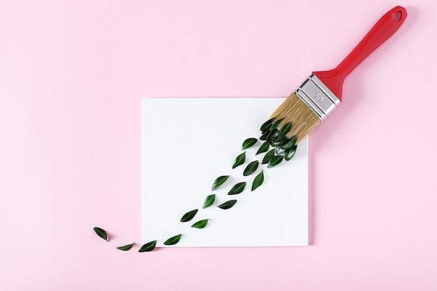 흰색 캔버스와 붓 위에 녹색 잎의 붓질로 만든 창의적인 레이아웃