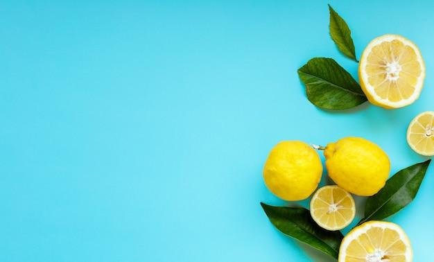 青い背景に分離されたカラフルなトロピカルフルーツで作られた創造的なレイアウト。最小限の夏のコンセプト。柑橘系の果物のパターン。フラットレイ、上面図。レモンスライスの背景。スペースをコピーします。