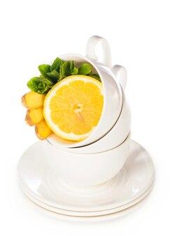 白地にミントティー、レモン、生姜のカップで作られた創造的なレイアウト。上面図。