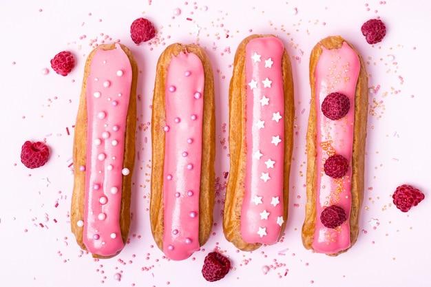 Креативный макет из эклеров с розовой глазурью на белом фоне. концепция питания.