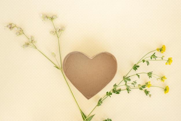 Творческий макет из цветов и листьев с шаблоном коробки сердца. плоская планировка.
