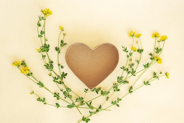 Креативный макет из цветов и листьев с подарочной коробкой в форме сердца.