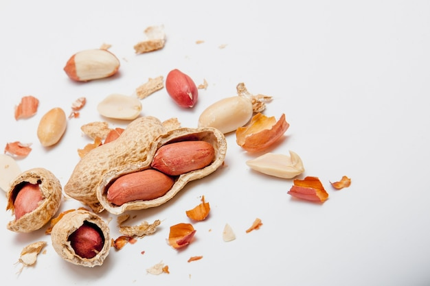 白い背景の上のヘーゼルナッツナッツ、アーモンド、クルミ、ピーナッツ、カシューナッツで作られた創造的なレイアウト