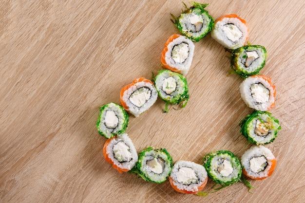 バレンタインデーのためのハート型の巻き寿司のセットで作られた創造的なレイアウト。