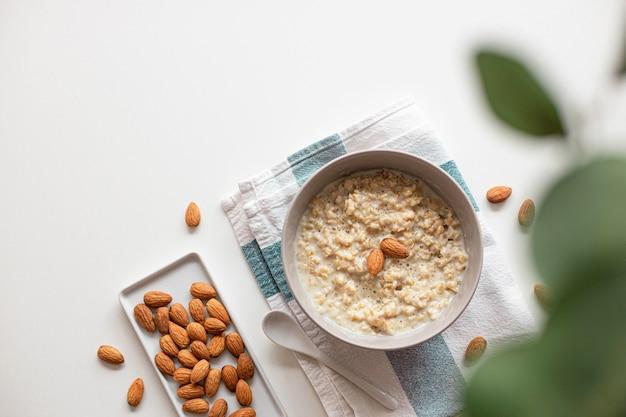 Креативный макет из домашней овсяной каши с ореховым миндалем в миске, керамической ложкой на белом