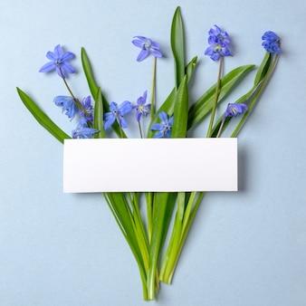 紫の春の花とパステルブルーの背景の空白の空カードで作られた創造的なレイアウト。