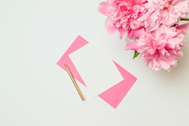 Creative layout made of pink paper envelope with a gold pen, a bouquet of pink peonies isolated on white