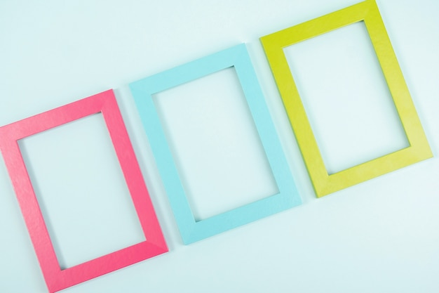 Creative layout made of three bright colored frames on blue background. flat lay top view copy space mockup.