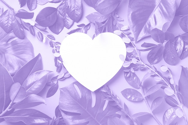 Creative layout made of tropical leaves, heart shaped paper in trendy violet color.