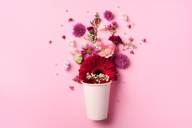 Creative layout made of white paper cup with pink flowers.