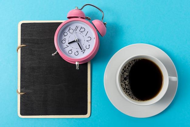 青い背景の上のコーヒーと目覚まし時計で作られた創造的なレイアウト。