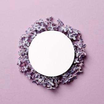 Творческий макет выполнен с сиреневыми цветами на ярко-фиолетовом фоне с пространством для текста. минимальная концепция весны.