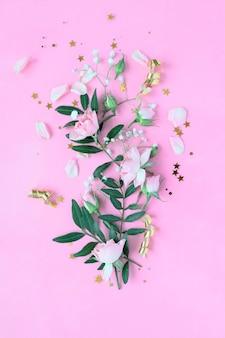 ピンクの背景にピンクと紫の花で作られた創造的なレイアウト。フラットレイ。春のミニマルコンセプト。