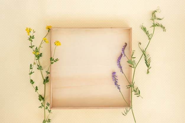 Creative layout made of wooden box and wild flowers and leaves with paper card note.