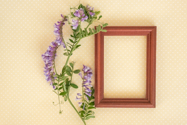 Creative layout made of wooden frame and wild flowers and leaves with yellow paper card note.