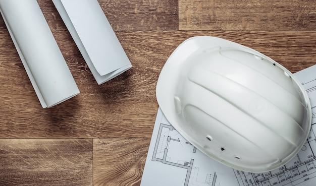 Креативный макет архитекторов с рулонными чертежами, планом архитектурного проекта, строительным шлемом на полу, рабочим местом. вид сверху. плоская планировка