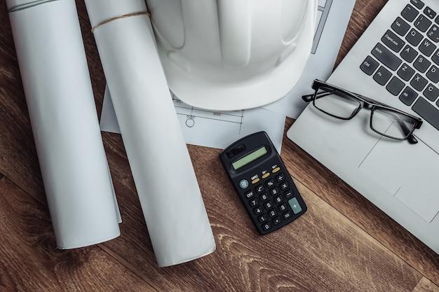 Креативный макет архитекторов с рулонными чертежами, план архитектурного проекта, строительный шлем на полу, рабочее место с ноутбуком. вид сверху. плоская планировка