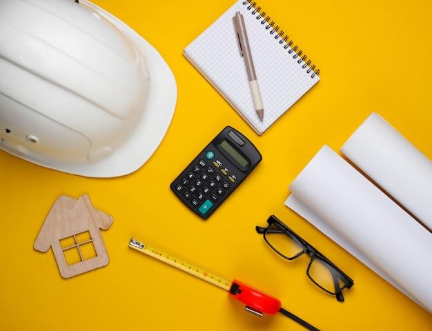 Креативный макет архитекторов с рулонными чертежами, планом архитектурного проекта, инженерными инструментами и канцелярскими принадлежностями на желтом фоне, рабочее пространство. вид сверху. плоская планировка