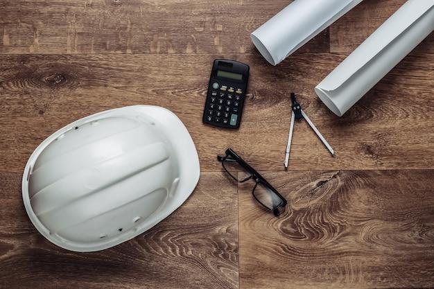 Креативный макет архитекторов с рулонными чертежами, инженерными инструментами и канцелярскими принадлежностями на полу, рабочем пространстве. вид сверху. плоская планировка.