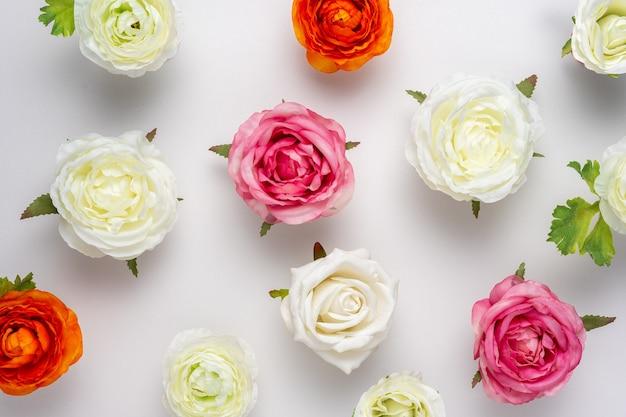 Творческий макет красивых розовых цветов на белой поверхности.