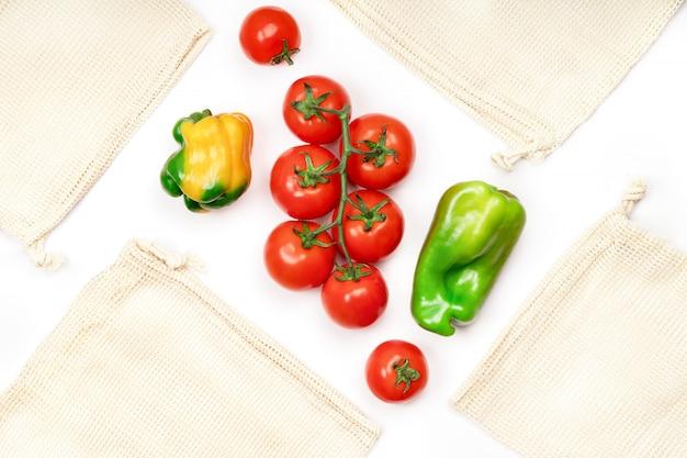 新鮮な野菜と白、トップビューで再利用可能な環境にやさしいバッグの創造的なレイアウト