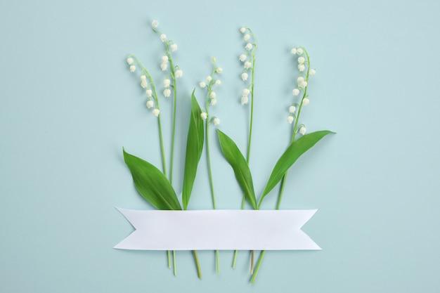 밝은 녹색 배경에 은방울꽃의 창의적인 레이아웃