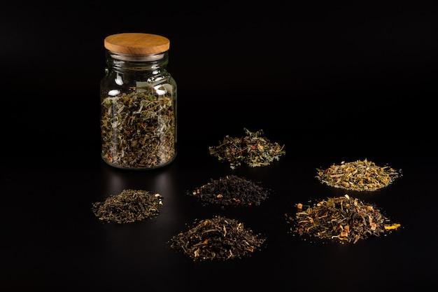 黒の背景にルーズティー緑茶紅茶フルーツとハーブティーの創造的なレイアウト