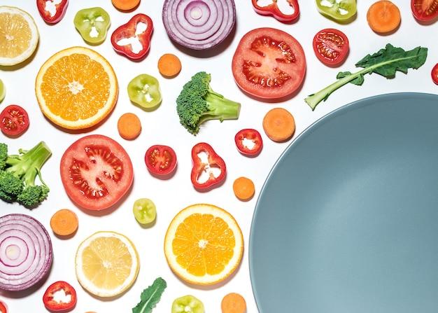 Творческий макет нарезанных овощей и фруктов с тарелкой на белой поверхности.