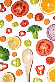 Творческий макет нарезанных овощей и фруктов деревянной ложкой на белой поверхности.