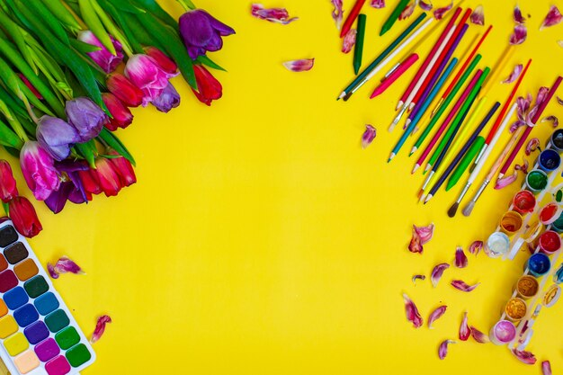 노란색 표면에 수채화 팔레트, 페인트 브러시 및 튤립 꽃이있는 창의적인 레이아웃