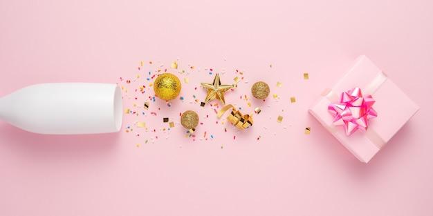 Креативный макет с бокалом шампанского, подарочной коробкой и украшением с золотыми блестками.