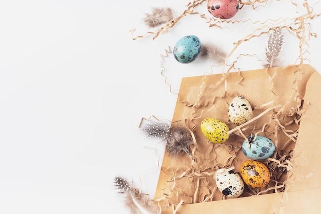 白い背景の上のペーパークラフトの封筒にイースターエッグ、干し草、ウサギ、羽とクリエイティブなレイアウト。コピースペースでお祝いのイースター作曲。フラットレイ、上面図。
