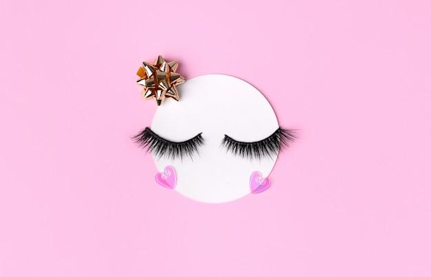 Креативный макет с ресницами. закрытые глаза на пастельно-розовом фоне